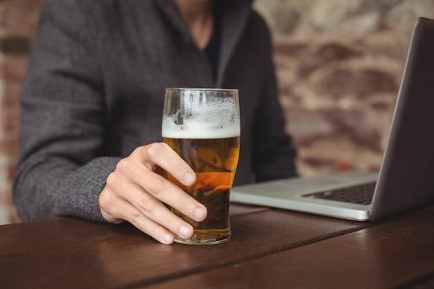 Homem segurando o copo de cerveja e usando o laptop Foto gratuita