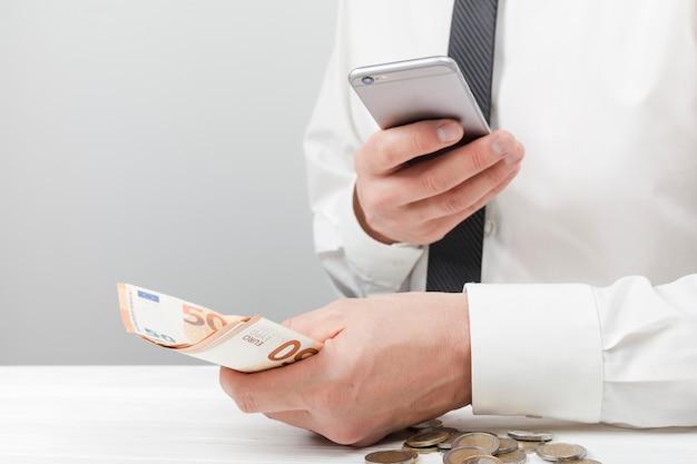Homem segurando o dinheiro e usando a calculadora Foto gratuita
