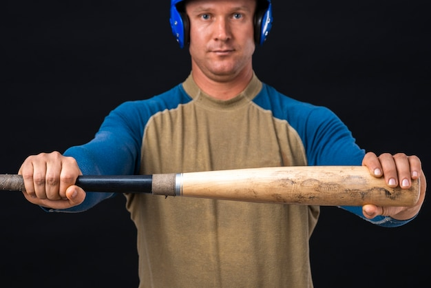Homem segurando o taco de beisebol horizontalmente Foto gratuita