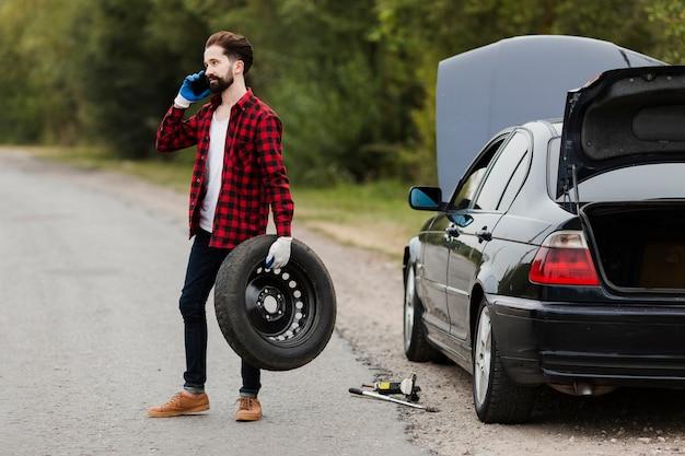 Homem, segurando, pneu, e, falando telefone Foto gratuita