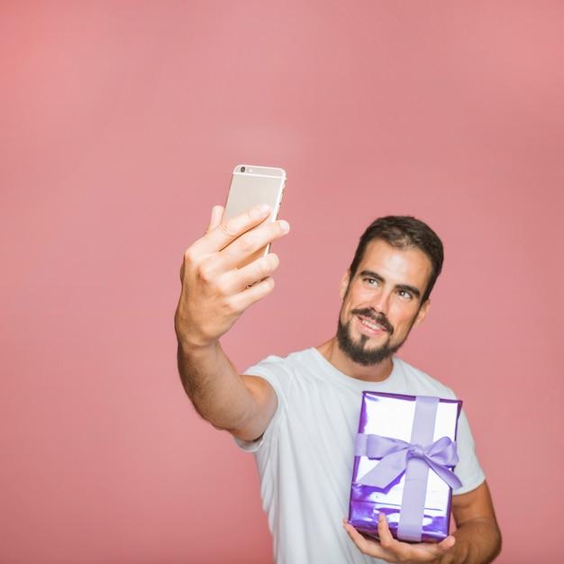Homem, segurando, presente, levando, selfie, contra, fundo cor-de-rosa Foto gratuita