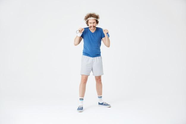 Homem segurando pular corda nas mãos. parecendo agressivo e motivado Foto gratuita