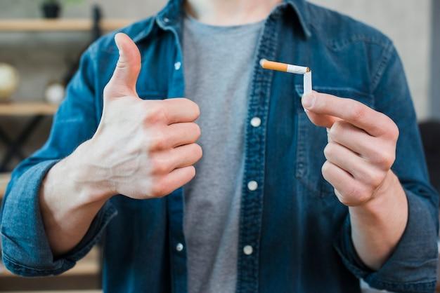 Homem, segurando, quebrada, cigarro, e, mostrando, polegar cima, gesto Foto gratuita