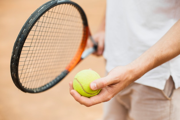 Homem segurando raquete e bola de tênis Foto gratuita