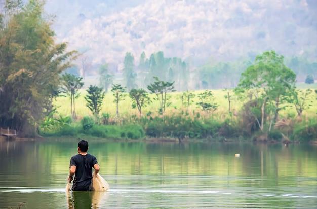 Homem, segurando, redes pescaria, andar, em, água fundo, montanhas borradas, e, árvores Foto Premium