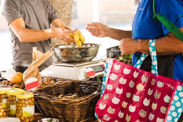 Homem, segurando, saco, comprando, bananas, de, vendedor fruta, em, mercado Foto gratuita