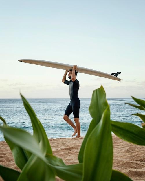 Homem segurando sua prancha de surf Foto gratuita
