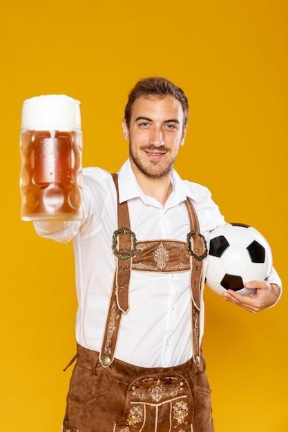 Homem, segurando, um, bola, e, cerveja, pint Foto gratuita