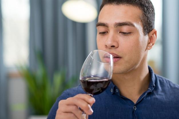 Homem segurando um copo de vinho tinto com espaço de cópia Foto gratuita