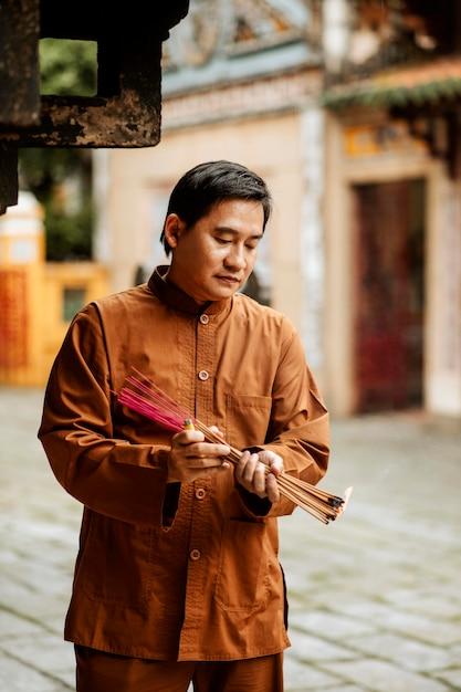 Homem segurando um pacote de incenso no templo Foto gratuita