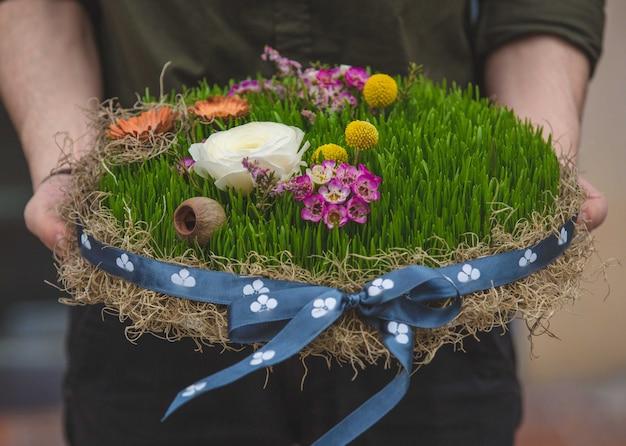 Homem segurando um prato de novruz símbolo semeni Foto gratuita
