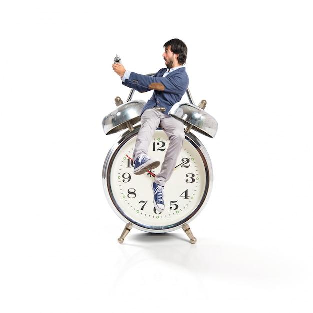 Homem segurando um relógio sobre fundo branco Foto gratuita
