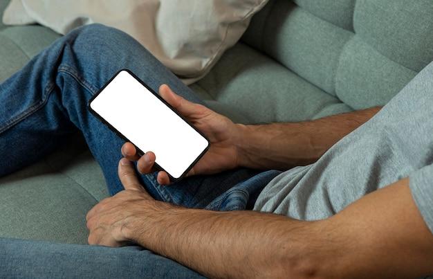 Homem segurando um smartphone enquanto está sentado no sofá Foto gratuita