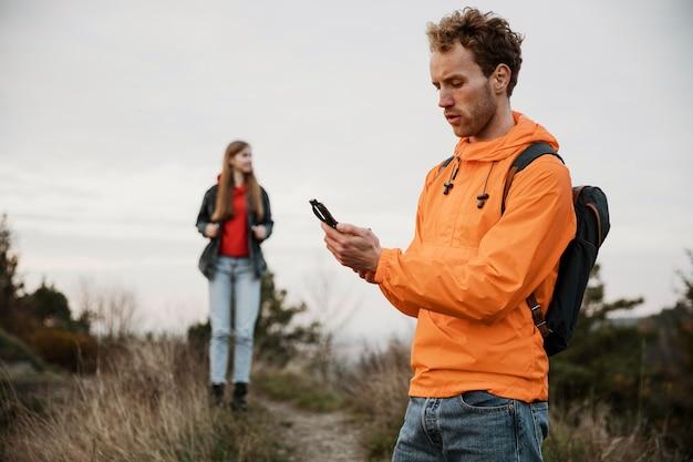Homem segurando uma bússola durante uma viagem com a namorada Foto gratuita