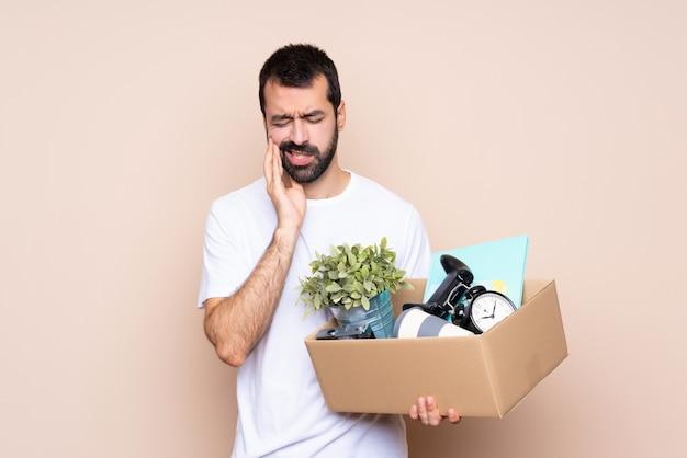 Homem segurando uma caixa e movendo-se em nova casa com dor de dente Foto Premium