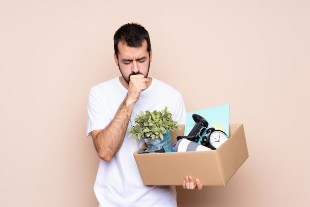 Homem segurando uma caixa e movendo-se em nova casa está sofrendo de tosse e se sentindo mal Foto Premium