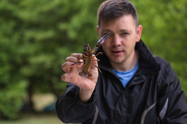 Homem segurando uma lagosta antes de liberá-lo para a liberdade Foto Premium