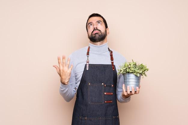 Homem segurando uma planta frustrada por uma situação ruim Foto Premium