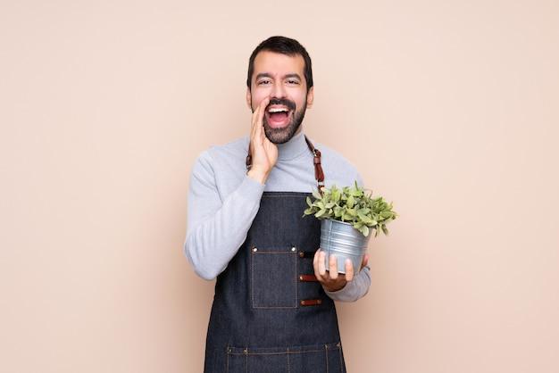 Homem segurando uma planta sobre parede isolada, gritando e anunciando algo Foto Premium
