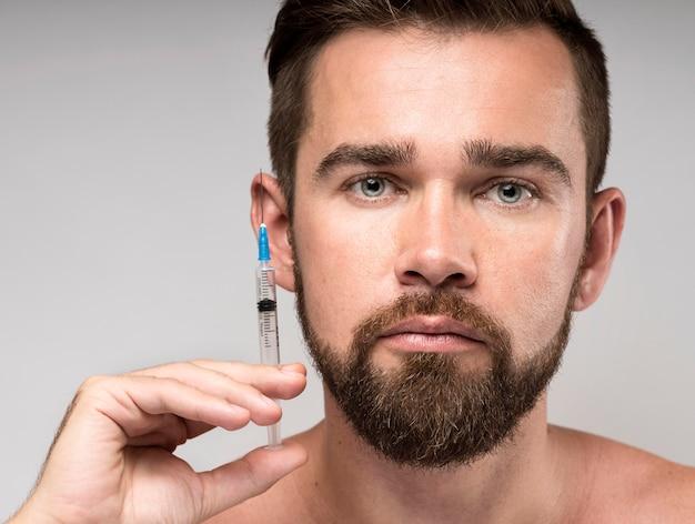 Homem segurando uma seringa perto do rosto Foto gratuita