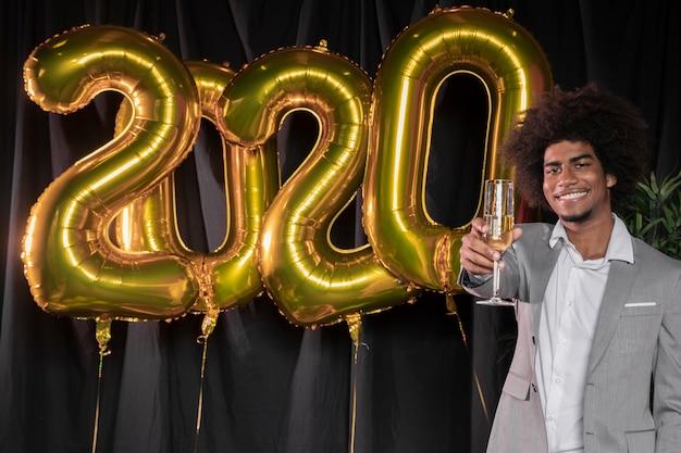 Homem segurando uma taça de champanhe e feliz ano novo 2020 balões Foto gratuita