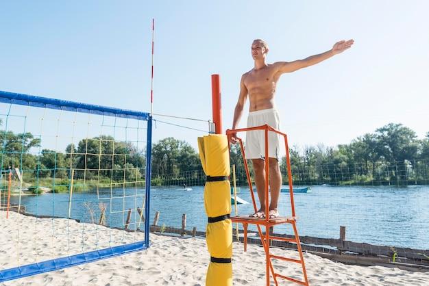 Homem sem camisa atuando como árbitro de uma partida de vôlei de praia Foto gratuita