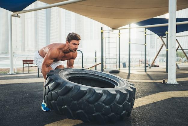 Homem sem camisa fazendo exercício e exercícios diferentes ao ar livre Foto Premium