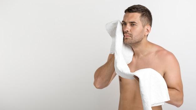 Homem sem camisa jovem sério, limpando o rosto com pé de toalha contra fundo branco Foto gratuita