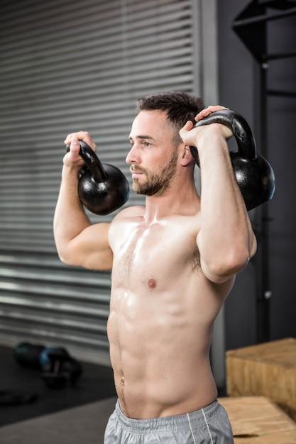 Homem sem camisa levantamento kettlebells no ginásio crossfit Foto Premium