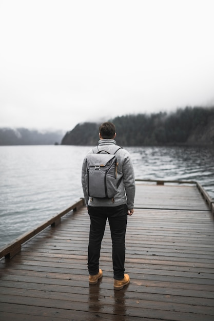 Homem sem rosto em pé no cais Foto gratuita