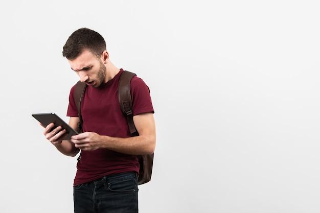 Homem sendo surpreendido e olhando para tablet Foto gratuita