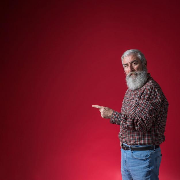 Homem sênior, apontar, seu, dedo, em, algo, contra, experiência vermelha Foto gratuita