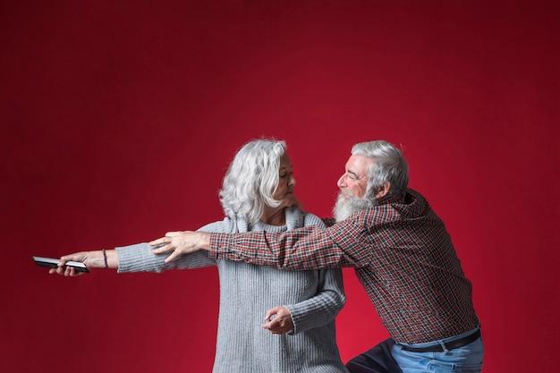 Homem sênior, arrebatando, a, controle remoto, de, seu, mão mulher, contra, vermelho, fundo Foto gratuita