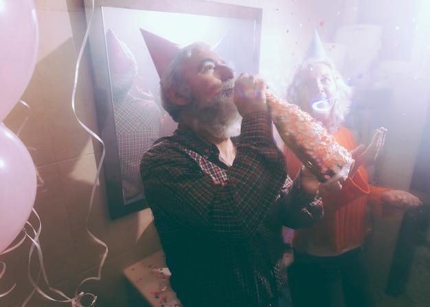 Homem sênior, bebendo, a, álcool, através, garrafa, com, seu, esposa, jogar, confetti, ar Foto gratuita