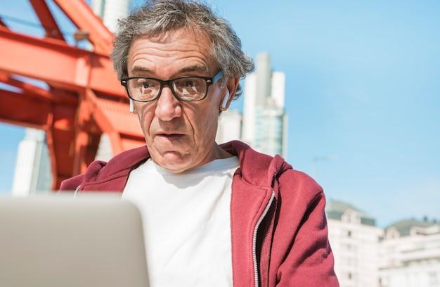Homem sênior chocado que veste óculos pretos que olha o portátil ... 35054090436