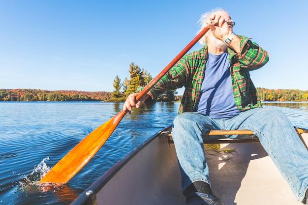 Homem sênior, com, canoa, remando, ligado, um, dia ensolarado Foto Premium