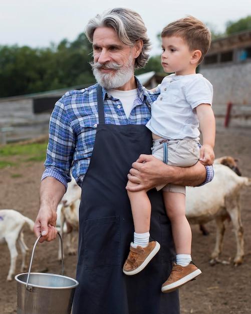 Homem sênior com neto na fazenda Foto gratuita