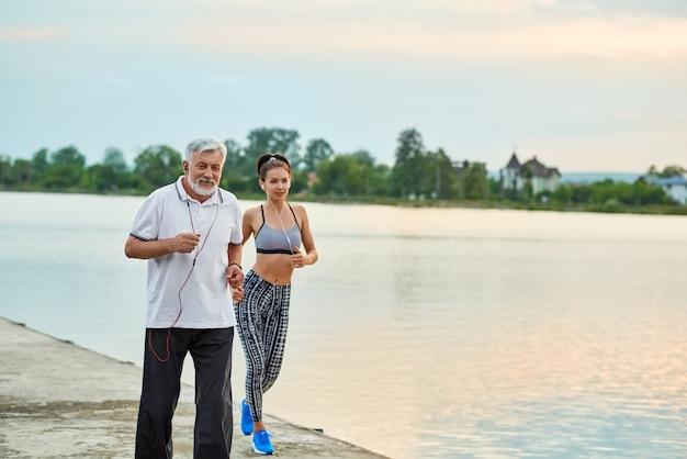 Homem sênior e jovem ativa correndo perto do lago da cidade. estilo de vida ativo, corpo saudável. Foto Premium