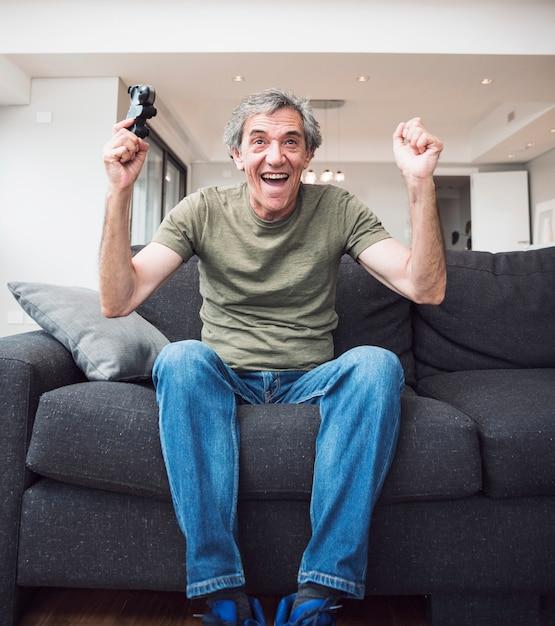 Homem sênior excitado que ganha o jogo video Foto gratuita