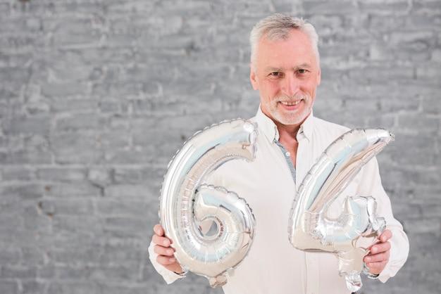Homem sênior feliz segurando balão de folha de prata em seu aniversário 64 Foto gratuita