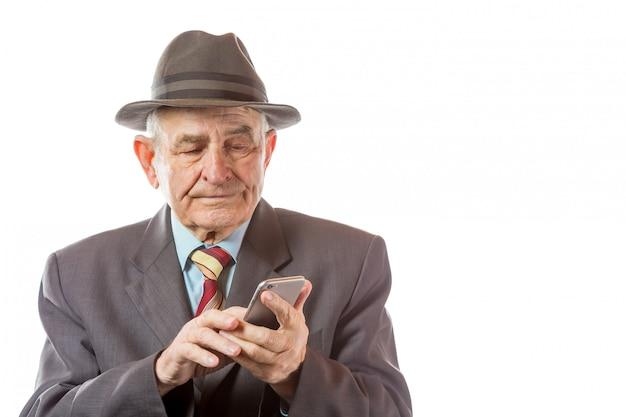 Homem sênior idoso no chapéu retrô usando seu telefone móvel isolado no fundo branco. Foto Premium