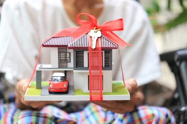 Homem sênior, mãos, segurando, modelo, casa, com, fita vermelha, e, a, car, com, teclas Foto Premium