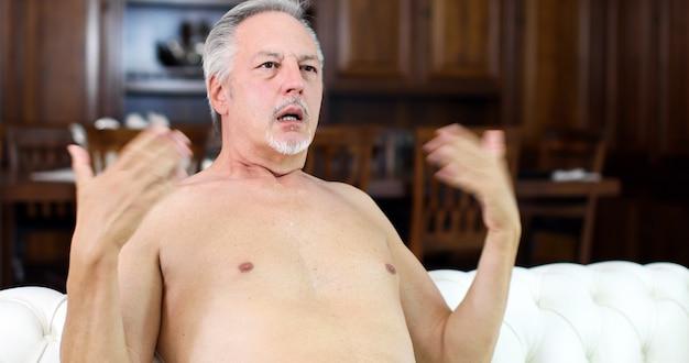 Homem sênior nu, sofrendo pelo calor enquanto está sentado em seu sofá Foto Premium