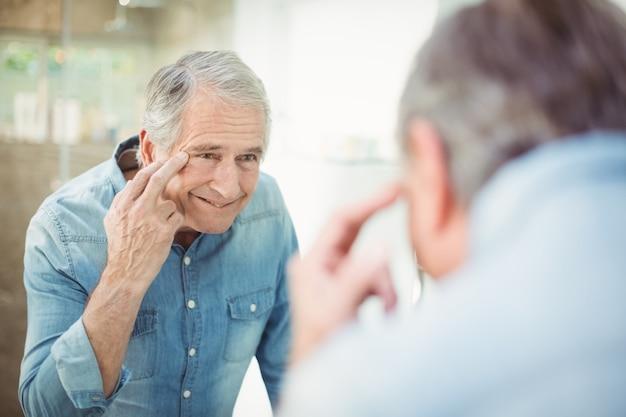 Homem sênior, olhando para a pele no espelho Foto Premium
