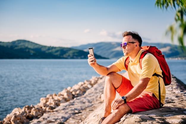 Homem sentado à beira-mar e tirar fotos com o telefone inteligente Foto Premium