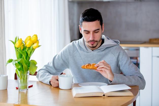 Homem sentado à mesa com uma xícara de café ou chá e comendo croissant. Foto Premium
