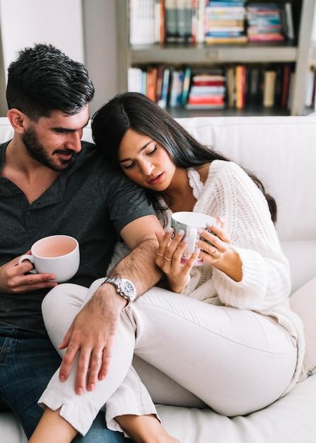Homem sentado com a namorada segurando copos de café na mão Foto gratuita
