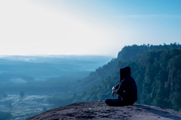 Homem sentado e assistindo o nascer do sol na falésia Foto Premium