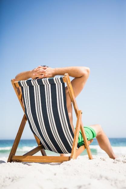 Homem sentado e relaxando na espreguiçadeira Foto Premium