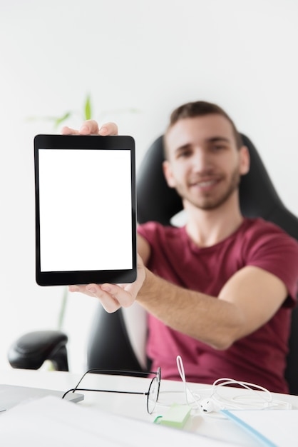 Homem sentado em uma cadeira de jogos e mostrando seu tablet Foto gratuita